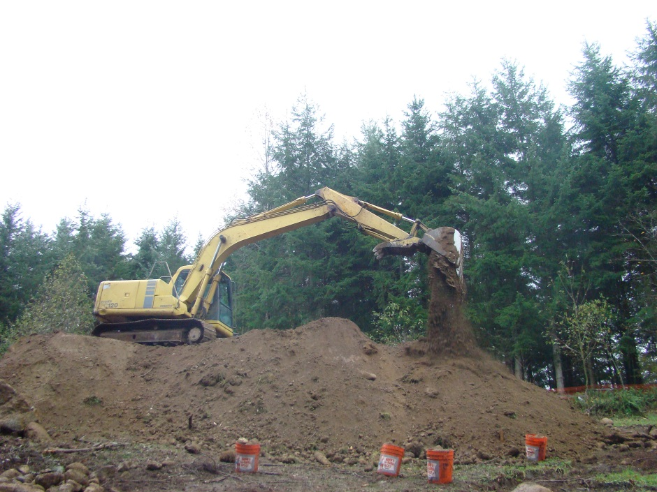 Excavator on mound dropping soil
